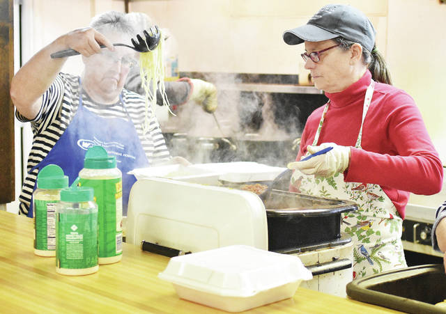 Linda Gephart, left, of Newport, and Bobby Bender, of Fort Loramie, fill up a to-go container with during the Newport Sportsmen Club's annual spaghetti dinner to benefit Wilson Hospice. Door prizes were handed out during the event held Sunday, Feb. 11