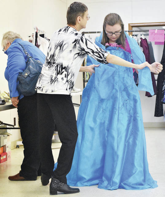 FISH volunteer Mary Miller, center, of Versailles, helps Harley Hines, 16, of Piqua, caregiver grandma, Kathy Hines, look at a prom dress for sale at a FISH Prom Dress Party sale located just a few doors down from the FISH store in the CVS Pharmacy complex. Looking over shoes to go with the dress is Hines' grandma Kathy Hines, of Piqua. Dresses at the sale were $10. Hines also bought blue earrings, a necklace and a purse to go with her dress. The sale was held Sunday, Feb. 11.