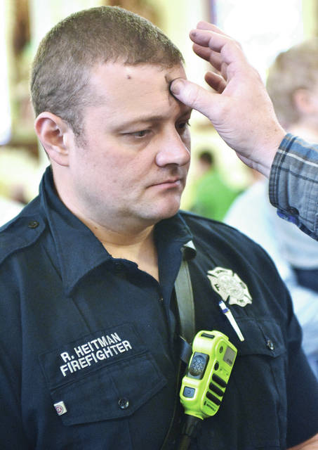 Sidney firefighter Ryan Heitman, of Houston, has a cross of ash drawn on his forehead by Don Vondenhuevel, of Sidney, during an Ash Wednesday service at Holy Angels Church Wednesday, Feb. 14. The ash cross symbolizes that people were made by God from dust and will return to dust. Ash Wednesday marks the beginning of Lent a time of abstinence and fasting.