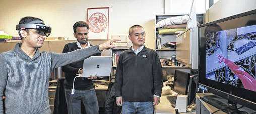 """Wright State researchers Miteshkumar Vasoya, left to right, Ashutosh Shivakumar and Yong Pei designed an augmented-reality system designed that puts a """"doctor in the house"""" to help recovering surgery patients manage pain without painkillers."""