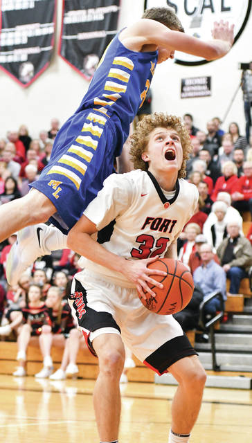 Fort Loramie senior guard Dillon Braun shoots as Marion Local's Nick Tangeman leaps over him during a nonconference game in February. Braun was named the Division IV player of the year.