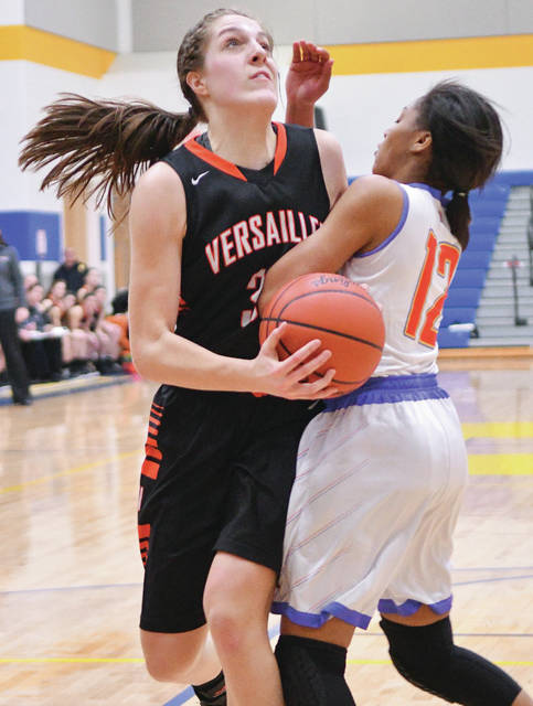 Versailles senior center Danielle WInner drives in the lane against Purcell Marian's Santia Cravens during the first half of a Division III district final on Monday at Springfield High School.