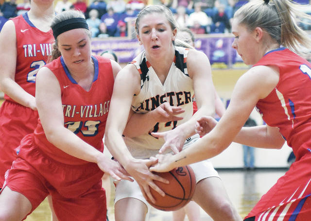 Minster's Paige Thobe works to keep the ball from Tri-Village's Maddie Downing, left, and Emma Printz during a Division IV regional semifinal on Thursday at Vandalia-Butler's Student Activities Center.