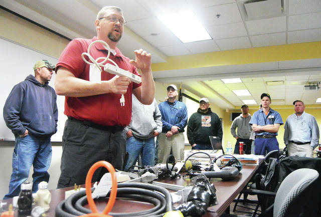 Compliance Safety and Health Officer Roy Williams, of Mansfield, holds up a power strip as he talks about how easily they can be overloaded. Williams was a speaker during OSHA training for city of Sidney employees at the Sidney police station Tuesday, March 13.