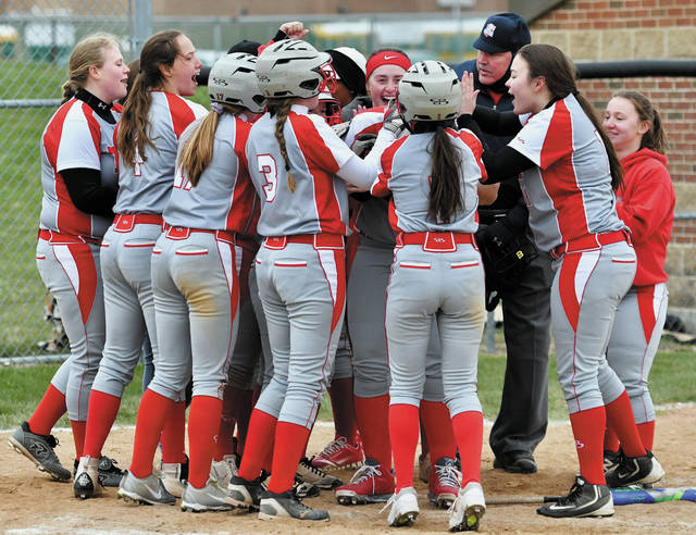 Troy players crowd around Tia Bass after she hit a grand slam in the seventh inning of a Greater Western Ohio Conference American North Division game on Tuesday at Aschenbach Field.
