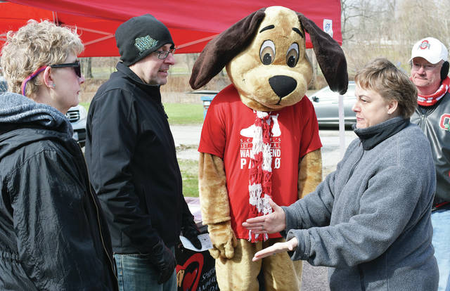 Talking, left to right, are SCARF member Becky Kubichek, of Sidney, Joe Laber, of Troy, Scarfie, Jackie Gaier, of Piqua, and SCARF board member Bob Baird, of Sidney. Gaier stopped by SCARF monthly cans for canines event at the Shelby County Animal Shelby Saturday, April 7 to drop off a check for $4,275. Gaier raised the money with help from her friend Nicole Bolin through a quarter auction at the Miami Valley Centre Mall recently. The money will go to SCARF's Building a Pawsitive Future Capital Campaign.