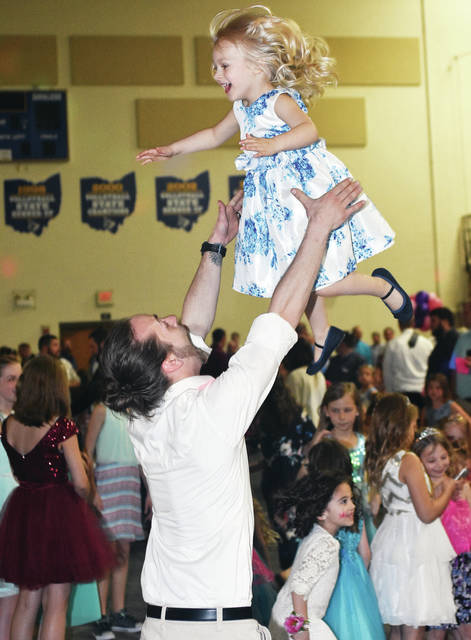 """Gaige Overton, left, tosses his daughter Lindyn Overton, both of Sidney, into the air as they dance during the very popular Gateway Arts Council's father-daughter dance """"Princess Ball"""" at Lehman Catholic High School Friday, April 13. Girls also made crafts played games and ate at the dance. Lindyn is also the daughter of Nikole Overton."""
