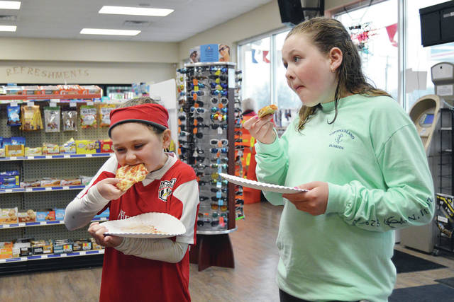 Eden Westerheide, left, 9, and her sister Eliza Westerheide, 11, both of Sidney and the children of Anne and Jay Westerheide, eat some of the pizza that was being handed out for free during a 10 year anniversary celebration held by East 47 Marathon Saturday, April 14. The event was held April 13 - 15. There were was also free hot dogs and wings. A raffle was also held.