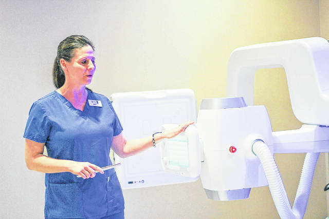 Amy Magoteaux, a radiology technician at Orthopedic Associates of SW Ohio, demonstrates the latest in X-ray technology during an open house and ribbon cutting, Thursday, April 12, at the firm's new location in Sidney, 300 3rd Ave.