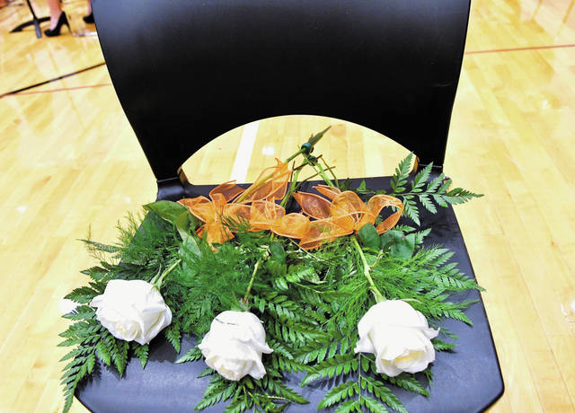 Three roses were placed on a chair before Versailles' graduation ceremony on Sunday in memory of Zach Kelch, who died in 2017. Kelch would have graduated on Sunday.