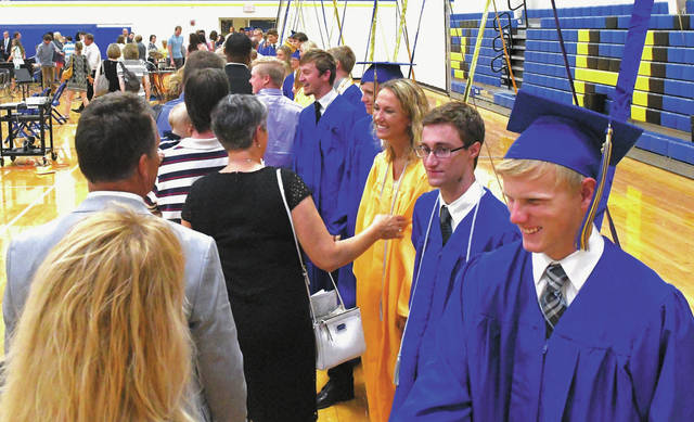 Russia graduates are congratulated by spectators during the recessional after Russia's graduation ceremony on Sunday at Clair C. Naveau Gymnasium.
