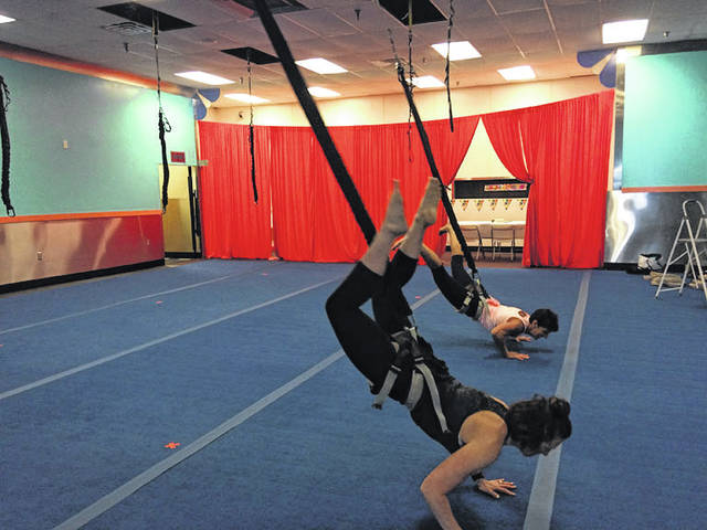 Chariti Moon, left, and Kathy Wallace, both of St. Marys, demonstrate an exercise using bungee cords. Wallace has opened Heart and Sole Aerial Bungee Fitness Studio LLC in St. Marys.