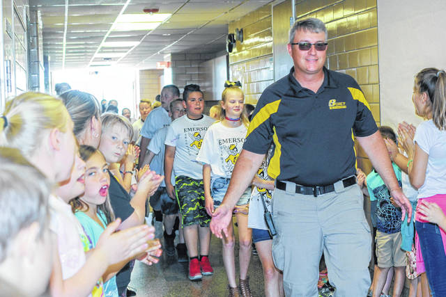 Emerson Elementary School Principal Michael Moore leads the fourth-grade students out of the school during the Clap Out signifying their last day at the school Thursday, May 24.