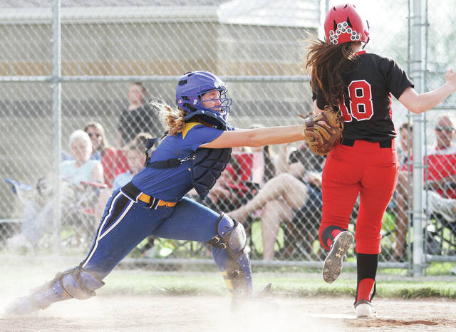 Russia's Lauren Monnin tags Newton's Carley Marple just as Marple reaches home plate during a Division IV sectional final on Tuesday in Bradford.