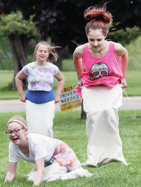 Taking part in a sack race are, left to right, Olivia Breinich, 10, daughter of Ben and Amy Breinich, Shyanne Moon, 11, daughter of Brandon Moon and Melissa Wooten, and Destiny Fahnestock, 11, all of Sidney, daughter of Matt and Nicole Fahnestock. The sack race was one of many outdoor activities Whittier Elementary students took part in Wednesday, May 16 for Fun and Field Day. Kids also drew with sidewalk chalk and bounced on rubber balls. The event is put together by the Whittier PTO.