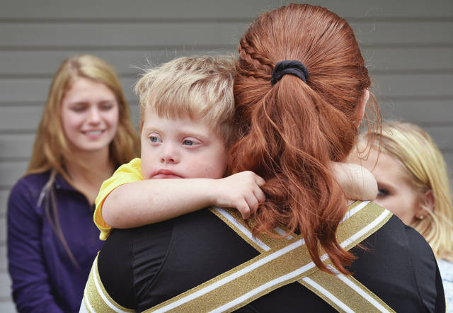 Grant Topp, left, 4, son of Mary and Eric Topp, is held by Botkins cheerleader Meg Russell, 15, both of Botkins, daughter of Holly and Mark Russell, during Walk Your Socks off for Down Syndrome Awareness Saturday, May 19. The event featured free food, flower planting, face painting, dancing, corn hole, and two bounce houses. The event was held at Ohio Living Dorothy Love.