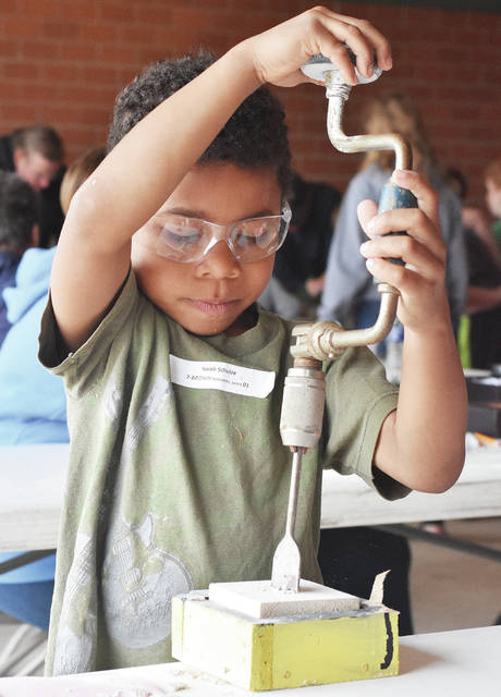 Isaiah Schulze, 7, of Anna, son of Krista and Brian Schulze, tries his hand at making a candle holder by drilling a hole during Manufacturing Day at Anna Elementary Friday, May 18. The Shelby County Historical Society event took kids through all the steps for designing, building, packaging and selling a product.