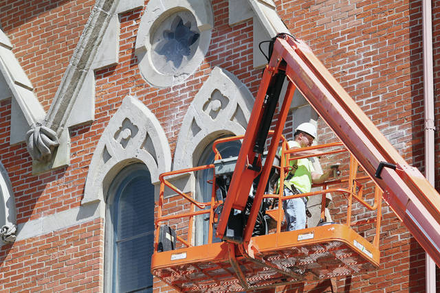 Mike Snow, of Houston, gets a scoop of mortar ready with his trowel before applying it to the joints between bricks on the Monumental Building Thursday, May 24. The Monumental Building was the first of 14 Civil War buildings built in Ohio. The cornerstone was laid in 1875. An Opera Hall located on the third floor is now used as a courtroom. Old mortar in-between bricks on the building is being removed and replaced.