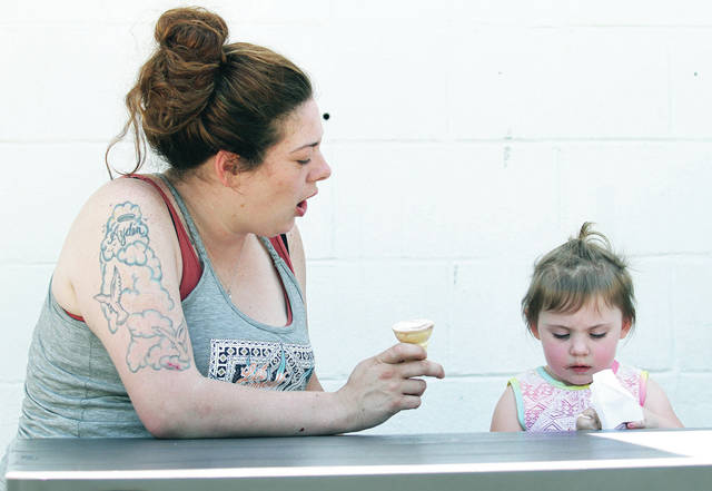 Sierra Geuy, left, reacts as her daughter, Noelle Pike, 2, both of Sidney, tries to clean the ice cream off the top of her cone at Chilly Jilly's Friday, May 25.