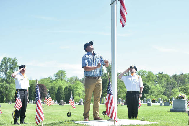 Navy Vet Joe Everett lowers the U.S. flag to half staff as Army Vet Bob Shoffner, left, and Marine Corp. Vet Josh Roth, all of Sidney, salute the flag during a Memorial Day service at Plattsville Cemetery Sunday, May 27. The guest speaker was retired Navy Commander Keith Putnam, of Conover. Taking part in the ceremony were members of the Sidney American Legion, AMVETS and VFW.