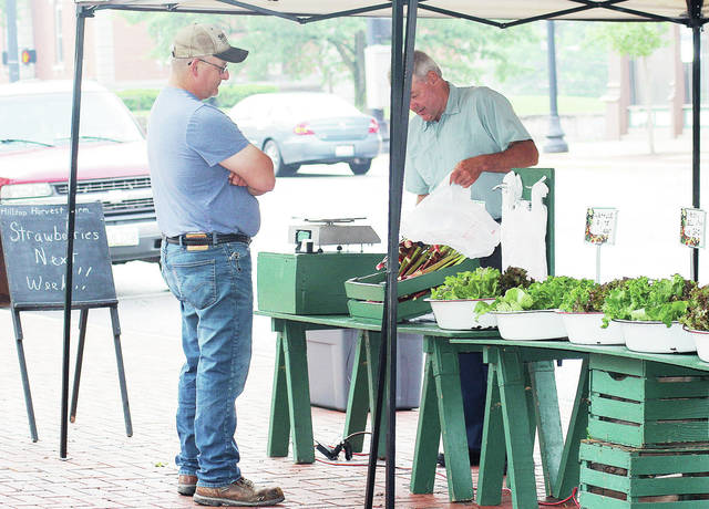 Jason Frantom, left, of Sidney, purchases some Rhubarb from Tom Brown, of Wapakoneta, at a Hilltop Harvest Farms stand at the 2017 Sidney Farmers Market in downtown Sidney. This year's farmers' market opens for the season Saturday, May 26.