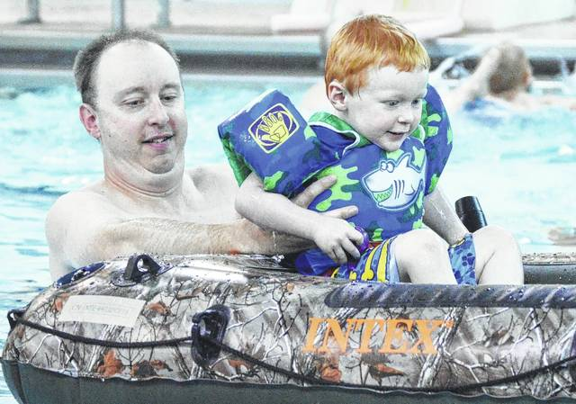 Jeff Bradley, left, places his son Damon Bradley, both of Sidney, son of Dr. Rosy McCarthy, into an inflatable raft during a 2017 Splash class at the Sidney-Shelby County YMCA. The raft was used to help teach kids to get into the habit of asking for permission to enter the water with a lifejacket on before getting into a boat.