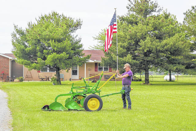 "Jerry Schmidt, of Sidney, who served in the U.S. Army for 6 years as an 4F, hangs a flag on a plow given to him by his father. ""I want people to know why we hang the flag. It's called freedom and respect,"" said Schmidt."