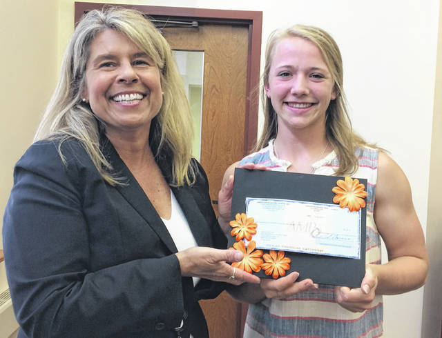 American Municipal Power representative Marni Hollman presents Minster student Grace Butler with the $2,500 Lyle B. Wright scholarship during Tuesday's Minster Council meeting.