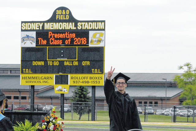 Sidney High School graduate Noah Ulrey gives a peace sign while standing in front of the scoreboard at Sidney Memorial Staduim during Saturday's graduation ceremony.