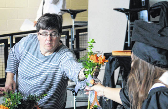 Jackson Center Senior Adviser Susan Harris passes out flowers before graduation ceremony Sunday afternoon.