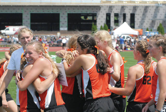 Members of Minster's track and field team hug after winning the Division III team title on Saturday at Jesse Owens Stadium in Columbus.