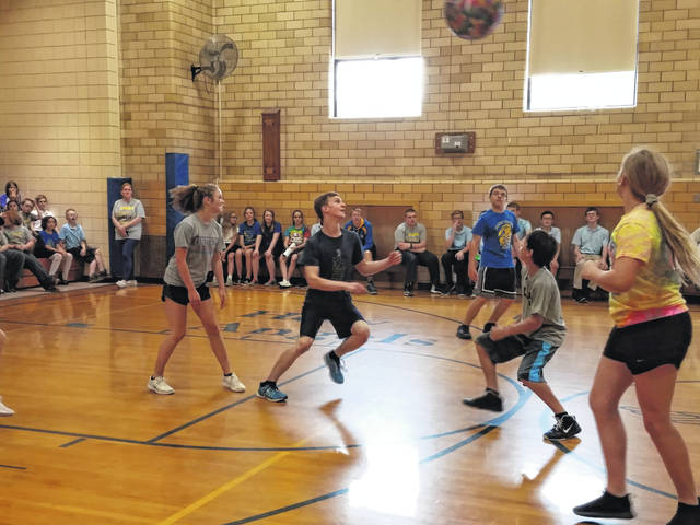 """As one of their last school activities, eighth-grade students, top photo, took on the Holy Angels faculty in the end–of-year yeachers vs. eighth-grade volleyball game. This annual event took place in the HA gymnasium. According to some sources, the teachers were reported to have won all three sets. Well, no matter who you got your 'scores' from, the games were enjoyed by all. Following this friendly rivalry, the eighth-graders, bottom photo, received an honorary """"clap out"""" of the building at the end of the day."""