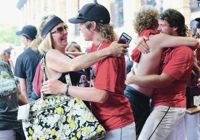 Shelly Barhorst, left to right, gives her son Ben Barhorst a hug on Saturday outside Huntington Park in Columbus after Fort Loramie beat Hicksville 8-4 in the Division IV state championship game. Fort Loramie fan Weston Rittenhouse, back right, gives CJ Billing a hug as well.