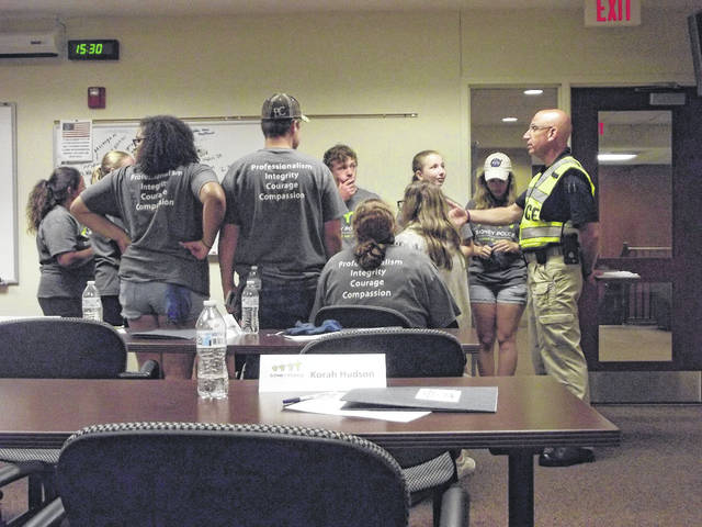 Community Resource Officer Mike McRill speaks with participants of the Teen Law Enforcement Workshop on Tuesday, June 5, following the Mock Crime Scene scenarios. Brock Rogers and Mallory Godwin can be seen looking toward Officer McRill as he briefs the students on how to handle themselves in a criminal investigation, pulling examples from the staged scenarios they participated in moments earlier. The students acted out various roles of law enforcement and first responders on the scene of hypothetical crimes, including a stabbing in a coffee shop and discovery of a dead body within a vehicle.
