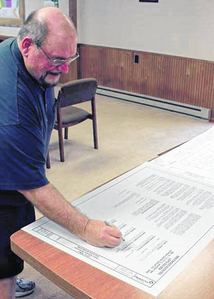 Jackson Center Zoning Officer and Community Development Director Ed Maxwell signs the final plat document for Westwood Estates, a new housing subdivision to be located in the southwest corner of town, June 11.