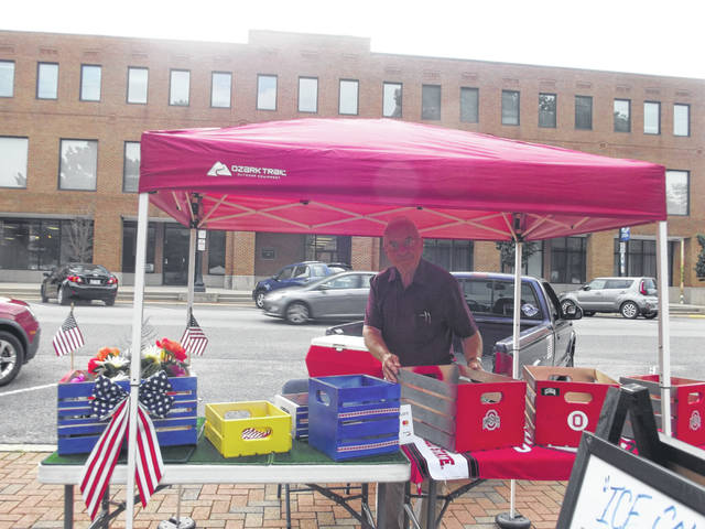 Blaine Batchelder sets up his decorative crates at the Great Sidney Farmers' Market. Batchelder enjoys meeting new people at the market.