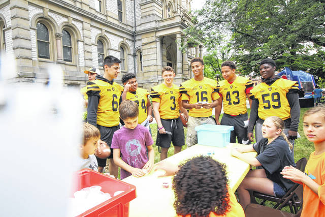 Members of the Sidney High School football team hand out flyers out for the Friday Night Lights event planned for July 13 from 7:30 to 10 p.m.