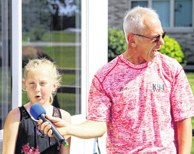 "Terry Stewart, right, of K94 Radio in Celina, reacts as Lilly Wilker, 12, of New Bremen, does her imitation of a dolphin at the Moeller Brew Barn in Maria Stein, Friday, June 1. Lilly will appear on ABC-TV's ""America's Got Talent,"" Tuesday, June 5."