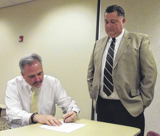 "New Sidney City Schools Superintendent Robert ""Bob"" Humble, right, watches as Board of Education President Bob Smith signs Humble's three-year contract with the district. Humble will officially begin his new job on Aug. 1 and will work up to 10 days during the month of July."