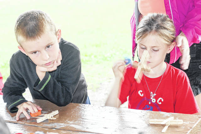 Karston, 7, and Peyton Duckroo, 9, create catapults using craft sticks and rubber bands during a Sidney Parks and Recreation Deparment activity, Monday, June 11, in Orbison Park. They are the children of Heidi and Matt Duckroo.