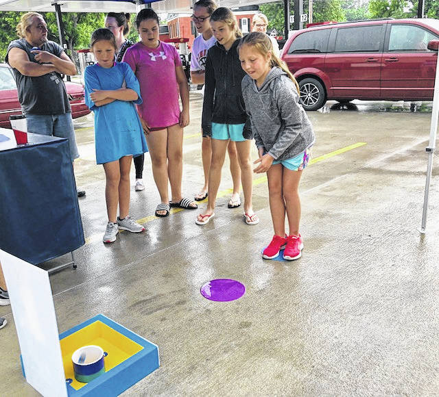 While the rain stopped Mr. Peanut from visiting with customers at Casey's General Store in Fort Loramie Thursday, there were still plenty of games to be played. Taylor Schmitmeyer, 11, tosses peanut coins into a can to see if she can win a pack of Planters Cashews. Her sisters, Alyson, 14, and Julia, 11, wait their turn, as do their friends, Keira, 10, and Kentleigh Eilerman. The Schmitmeyer girls are the daughters of Tony and Janine Schmitmeyer, and the Eilermans are the daughters of Scott and Jessica Eilerman, all of Fort Loramie.