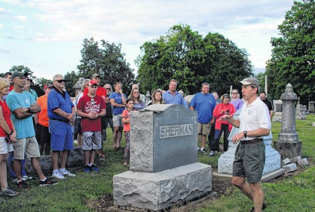 Rich Wallace, secretary of the Shelby County Historical Society, addresses a large crowd at the grave of the first soldier from Sidney to die in World War I during a tour at Graceland Cemetery Wednesday night. Wallace talked about how ethnicity brought division among residents in Sidney and Shelby County at the onset of the war.