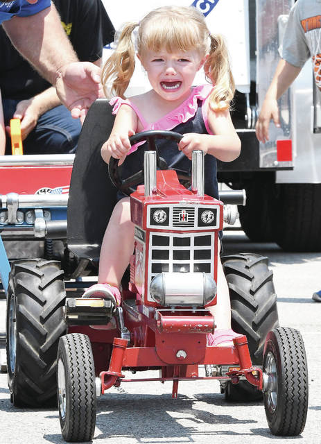 Annabelle Frilling, 2, of Botkins, gives it everything she has in the tractor pulls at Botkins Carousel Saturday, June 9. Annabelle insisted on pulling with the older kids. Annabelle is the daughter of Brooke and Matt Frilling. Additional photographs from the Carousel and Versailles Poultry Days appear on Pages 10-11.