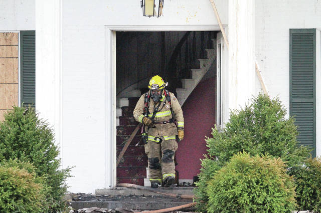 A Sidney firefighter leaves 2401 Wapakoneta Ave. after a fire rekindled Tuesday, June 12. The house is being used for fire experiments.