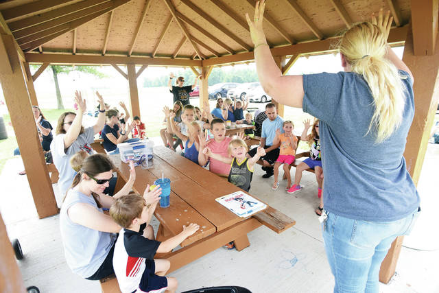 "Amos Memorial Library children's librarian Mandy Morgan, of Sidney, gets the attention of kids at Riverbend Park Wednesday, June 13 before reading them ""I Want to Be a Rock Star."" The ongoing program is a collaboration between Sidney Parks and Recreation and Amos Memorial Library."