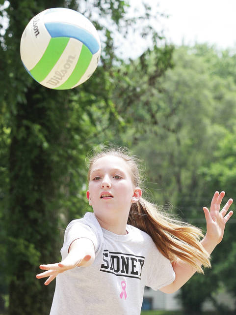 Hannah Weldy, 11, of Sidney, daughter of Travis and Jaime Weldy, practices her serve during a City of Sidney Parks and Recreation Department sand volleyball class Monday, June 25.