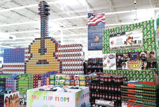 "The annual Country Concert Walmart display is now up. The display consists of a guitar and U.S. flag made of pop boxes. Also designed with pop boxes is the silhouette of a person saluting over the U.S. flag with the word ""Welcome"" underneath. Being sold in front of the display are things commonly seen at Country Concert such as folding lawn chairs, flip flops and coolers. Country Concert will be held July 5-7 in Fort Loramie."