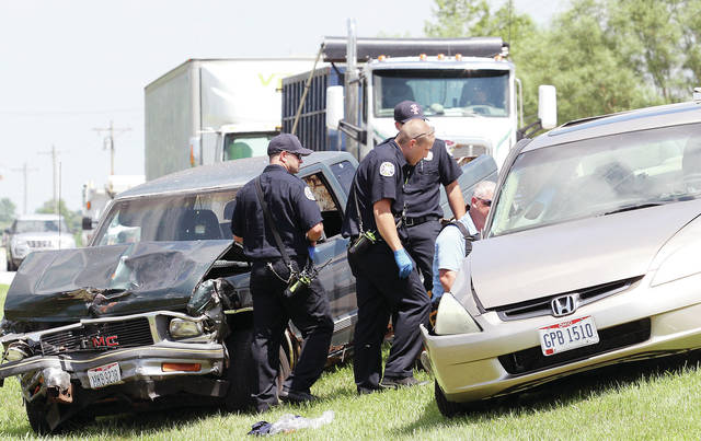 Sidney Fire Department medics and an Anna firefighter talk to a man who was involved in a crash involving a pickup truck and car at the intersection of state Route 119 and Sidney-Freyburg Road at about 2:40 p.m., Thursday, June 28. The Shelby County Sheriff's Office also responded to the scene and is investigating the crash.