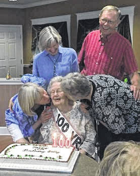 "Marcella ""Sally"" Thieman, center, of New Bremen, gets kisses from her daughters, Joan Forsthoefel, left, of Xenia, and Carol Hollingsworth, of Dover, Mass., as son, Bill Thieman, of Minster, and daughter Annette Pollack, of Concord, Mass., look on. Sally celebrated her 100th birthday, June 3, 2018, with family and friends during an open house at Elmwood Assisted Living in New Bremen."