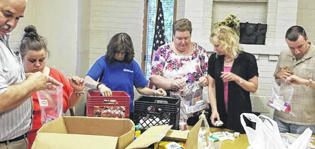 Members of the Shelby County Aktion Club fill blessing bags to be distributed to residents of Fair Haven, Ohio Living Dorothy Love and New Choices and for clients of FISH and the Veterans Association of Sidney. The club filled 130 bags with toiletries, snack foods and notes that were donated by area businesses. Picture are, from left, John Coffield, Tonya Dotson, Lesli Davis and Sara Mestemaker, all of Sidney, Julie Maurer, of Anna, and Eric Marshall, of Fort Loramie.